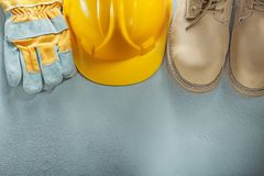 Hard hat protective gloves leather lace boots on concrete backgr Stock Photography