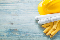 Hard hat rolled construction drawings protective gloves on woode Royalty Free Stock Photo