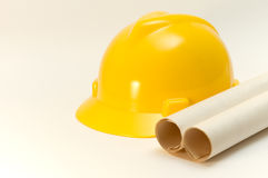 Hard hat and rolled plans. Yellow helmet and papel roll isolated over white Stock Image