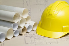 Hard hat and rolls of blueprints Royalty Free Stock Image