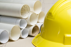 Hard hat and rolls of blueprints Royalty Free Stock Images