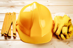 Hard hat, ruler and protection gloves on wooden background Stock Photo