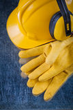 Hard hat safety earmuffs and yellow leather protective gloves on Stock Photo