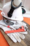 Hard hat,safety glasses,leather gloves and pipe wrench royalty free stock photos