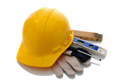 Hard Hat With Tools. A yellow contractors hard hat on work gloves and tools. Horizontal format over white with reflection Stock Photography