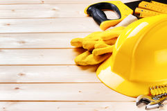 Hard hat and various tools on wooden background Royalty Free Stock Image