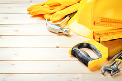 Hard hat and various tools on wooden background Stock Images