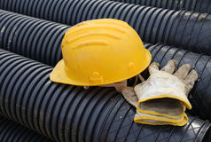 Hard hat and work gloves in construction site Royalty Free Stock Image