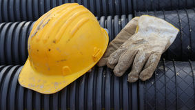Hard hat and work gloves in construction site Royalty Free Stock Photos