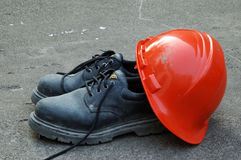 Hard Hat and Work Shoes. Construction safety equipment,a hard hat and a pair of safety shoes royalty free stock images