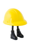 The Hard Hat Worker. A plastic model of a big yellow hard hat with two skinny little stick legs with black boots supporting it Royalty Free Stock Photography