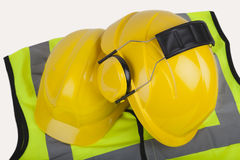 Hard hats and jacket. Isolated image of safety hats and hi-vis jacket Royalty Free Stock Photography