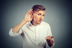 Hard of hearing man asking someone to speak up. Unhappy hard of hearing man placing hand on ear asking someone to speak up or listening to bad news, isolated on Stock Photography