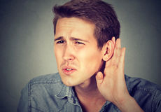Hard of hearing man placing hand on ear asking someone to speak up. Or listening to bad news, isolated on gray background. Negative emotion facial expression Royalty Free Stock Image