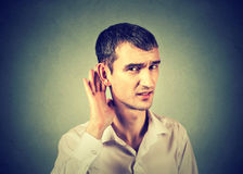 Hard of hearing man placing hand on ear asking to speak up. Unhappy hard of hearing man placing hand on ear asking someone to speak up or listening to bad news Stock Photo