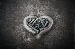 Hard Heart. A steel heart is full of nails on a metal background Royalty Free Stock Photos