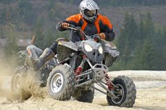 Hard left turn. Aggressive looking sport ATV splashing sand Royalty Free Stock Photos