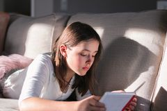 Hard light portrait of cute tween girl lying on sofa reading bookwith shadow on couch. royalty free stock images