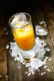 Hard Liquor Orange Juice Shooter. On a countertop with crushed ice and alcohol for drink concepts look at my portofolio royalty free stock photo