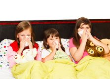 Hard Nose Blowing. Sick little girls suffering from bad influenza, staying in bed Royalty Free Stock Photography