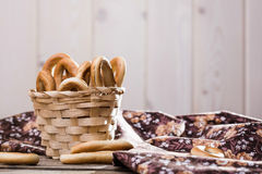 Hard oval cracknels in basket. Photo still life closeup basket full of delicious hard oval cracknels heaped high with some bagels lying on table near flowery Stock Photography