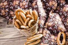 Hard oval cracknels in basket. Photo top view of hard oval cracknels in basket heaped high with some bagels lying on wooden table next to flowery cloth on rustic Stock Photography