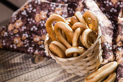 Hard oval cracknels in basket. Photo top view of hard oval cracknels in basket heaped high with some bagels lying on wooden table over blurred flowery cloth Royalty Free Stock Image