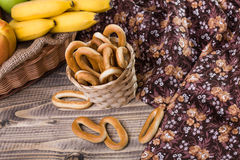Hard oval cracknels in basket. Photo top view of hard oval cracknels in basket with some bagels lying on wooden table next to flowery cloth and fruit plate in Royalty Free Stock Image