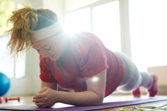 Hard Plank Exercise for Obese Woman. Portrait of young obese woman working out on yoga mat in fitness studio: holding plank exercise with effort to lose weight royalty free stock image