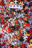 Hard Puzzle. Dice spelling out the word hard laying on top of red and gray scattered puzzle pieces. Copy space Royalty Free Stock Images