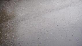 Hard Rain drops coming down on asphalt. Large Rain drops coming down grey asphalt with high speed stock footage