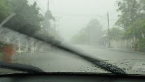 Hard rain falling through car windshield and wipe out. On street stock video