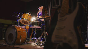 Hard rock music - drum break down performing - attractive girl with flowing hair. Backlight royalty free stock image