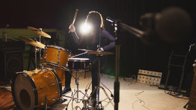 Hard rock music - drum break down performing - attractive girl with flowing hair. Backlight royalty free stock photo