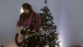 Hard rock and rock and roll. Slow motion. The teenage girl playing guitar, singing song and dancing near christmas tree. Hair flying in bright light. Happy new stock footage
