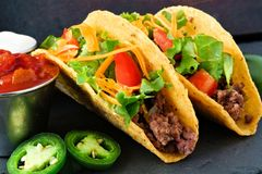 Hard shelled tacos with beef, lettuce, tomatoes and cheese close-up Royalty Free Stock Photo