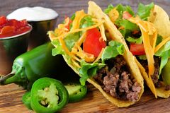 Hard shelled tacos with ground beef, lettuce, tomatoes, cheese close-up Stock Image