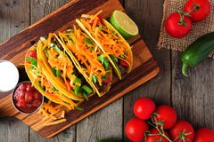Hard shelled tacos with ground beef, vegetables and cheese, overhead scene on over wood Stock Image