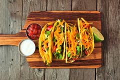 Hard shelled tacos with ground beef, vegetables and cheese, top view on a wood background Royalty Free Stock Image