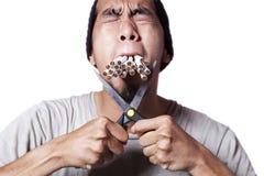 Hard smoker. Smoker cutting his cigarette to quit smoking Royalty Free Stock Photography