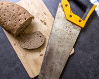 Hard stale bread and rusty hacksaw. Hard stale bread and cut off a piece of it lie on a wooden cutting board, rusty hacksaw lying beside Stock Image