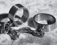 Hard steel handcuffs or cuffs. Hard steal or iron handcuffs or cuff laying in the snow royalty free stock image