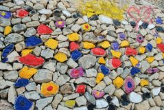 Amazing coloured stones wall: blue, yellow, red, black, grey, violet.
