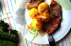Hard supper. Fried pork with fried onion with boiled potatoes; served with fresh vegetables like cucumbers Royalty Free Stock Image