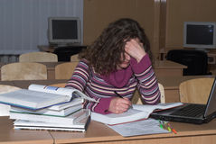 Hard thinking. Young female student is studying hard royalty free stock images