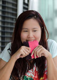 Hard thinking Asian woman. Asian woman is biting her pink small purse Stock Images