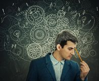 Hard thinking. Serious man over blackboard background gear brain arrows and mess as thoughts. Concept for mental, psychological development royalty free stock photo