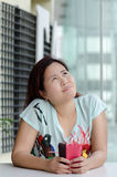Hard thinking woman. Asian woman is holding a pink purse and looking up Royalty Free Stock Image