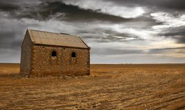Hard Times. An old farm building surrounded by dark clouds Royalty Free Stock Photo