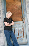 Hard Times. Blond woman leaning against rugged door frame with discouraged look. Concept of hard times and worry Royalty Free Stock Photo